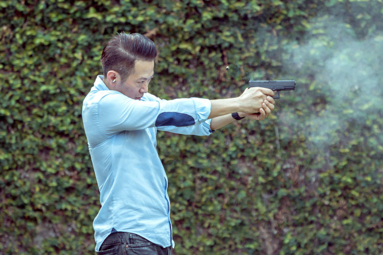 Man Aiming With Handgun While Standing Outdoors