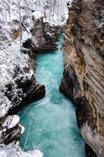 Fantastic Athabasca Falls creek while snowing, Jasper, Canada. Snow Blizzard Eroded Formation Purity Flowing Water Waterfall Turquoise Colored Non-urban Scene Sea Land Outdoors Travel Destinations Day Motion Scenics - Nature No People Nature High Angle View Beauty In Nature Rock Formation Solid Rock - Object Water Rock 17.62°