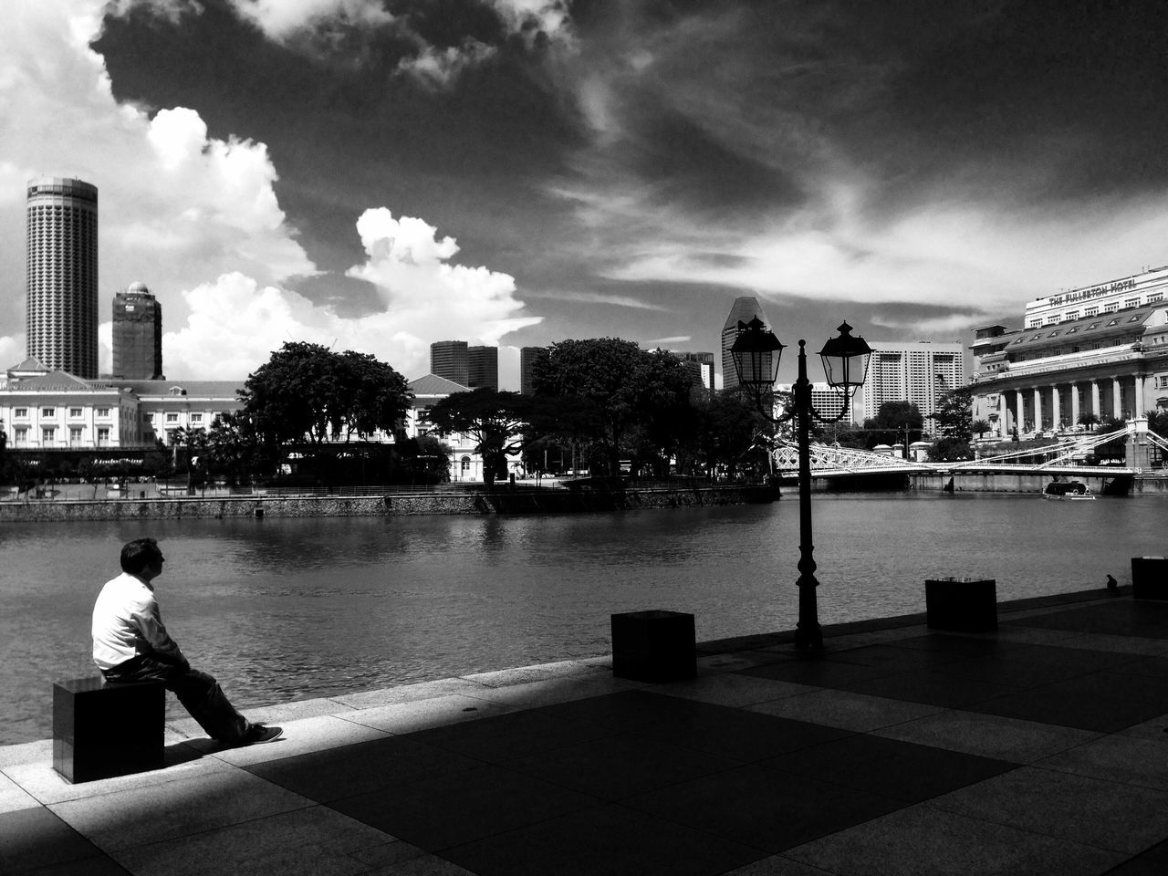 Full Length Of Man Sitting By River Against Sky In City