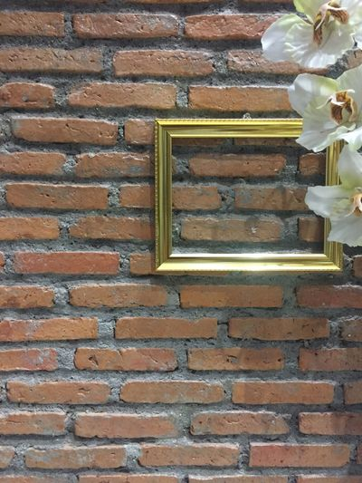 brown brick wall with gold frame and flower decoration. Built Structure Building Exterior No People Brick Wall Close-up Freshness Decorative Plants Textures And Surfaces Textures And Patterns Textured  Wall - Building Feature Beauty In Nature Plant Brick Wall Framed Brick Design Concept