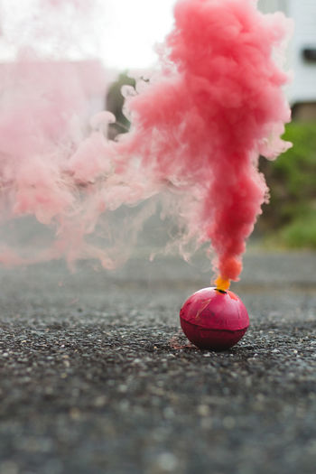 Close-up of pink smoke bomb on road