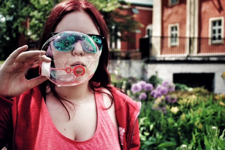 Portrait of young woman holding bubbles