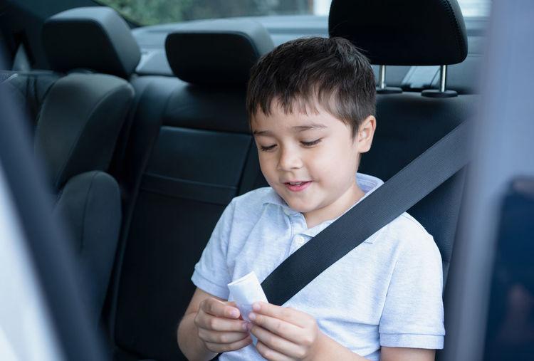 Full length of boy holding mobile phone in car