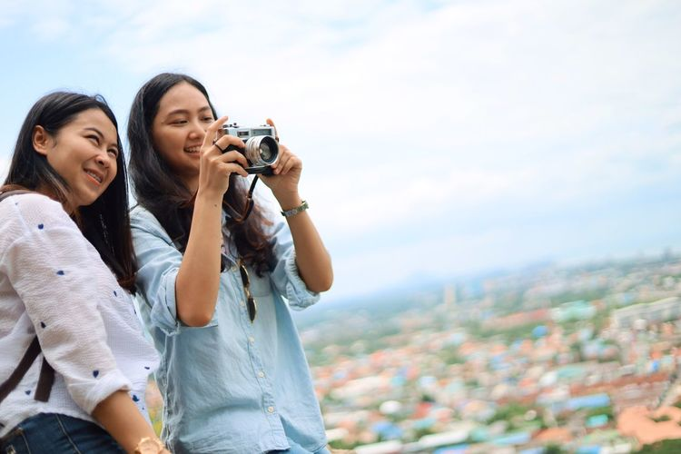 Two People Photography Themes Camera - Photographic Equipment Technology Photographing Sky Young Women Casual Clothing Young Adult Togetherness Architecture Adult Women City People Activity Leisure Activity Bonding Holding Positive Emotion Hair Digital Camera Cityscape Photographer Outdoors