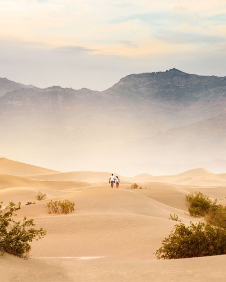 Rear view of people walking on desert against sky during sunset