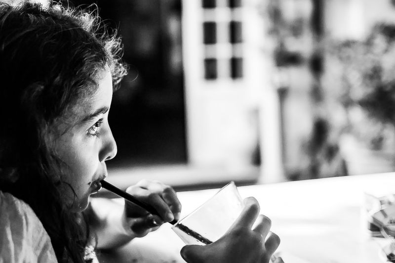 Close-up side view of girl drinking from straw