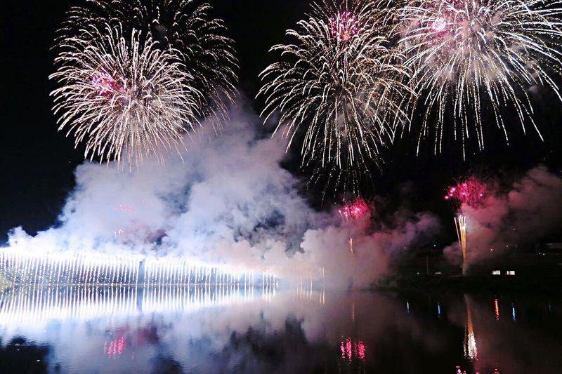 Idyllic view of firework display over sea at night