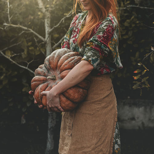 Midsection of woman holding pumpkin while standing outdoors