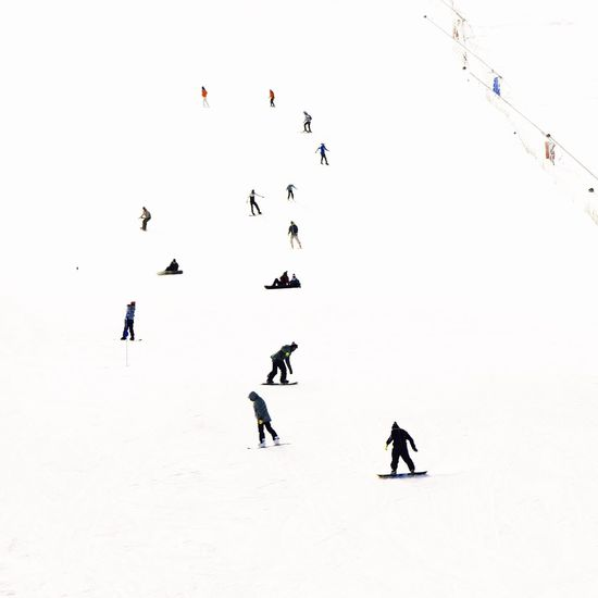 People skiing on field during winter