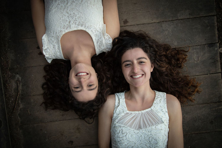 Directly above portrait of smiling twin sisters lying down on boardwalk