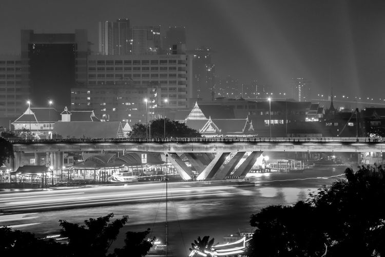 Black And WhiteNight Cityscape River and People on Bridge At Bangkok Built Structure Night Building Exterior Architecture Illuminated Water City Building Nature Reflection Sky Motion No People River Outdoors Street Tree Long Exposure Waterfront Cityscape Copy Space In Sky Bangkok