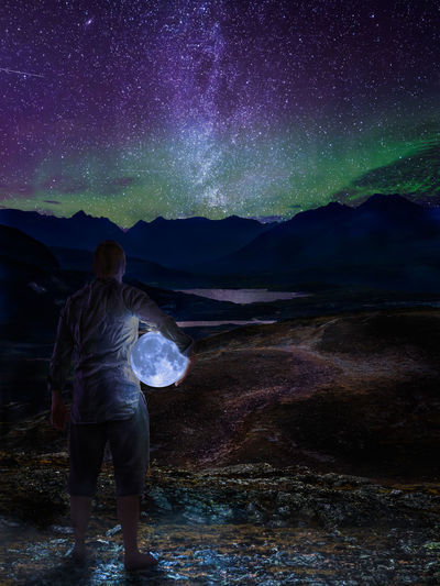 Digital composite image of man holding moon while standing on rock against sky at night