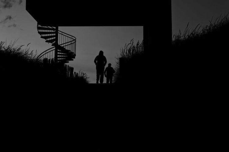 Walking through a gate Silhouette Architecture Sky Nature Real People Built Structure Lifestyles Low Angle View Walking Monochrome Blackandwhite Contrast Lonely Lost in the Landscape Lost Stairs Horizon Dark darkness and light Moody Gate
