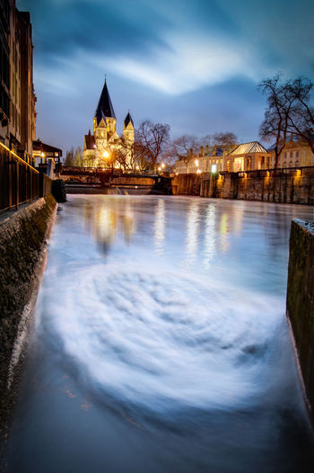 Illuminated Temple Neuf With Swirl Pattern In Moselle River