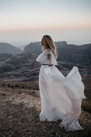 Woman standing on field by mountain against sky during sunset