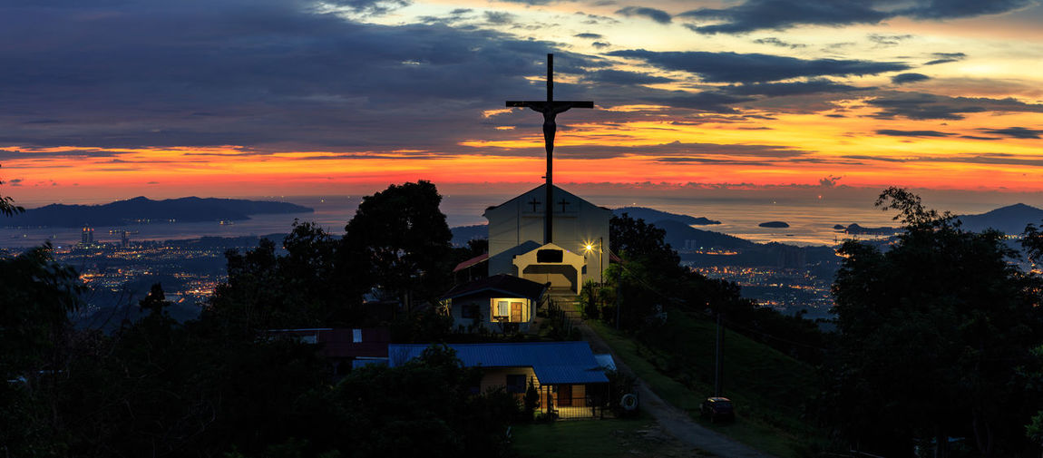 Crucifix on church against sky during sunset