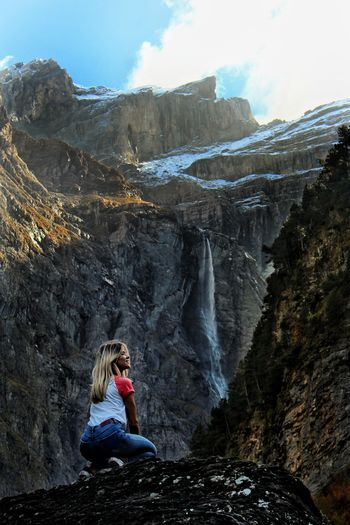Woman Kneeling On Rock While Looking At Mountains