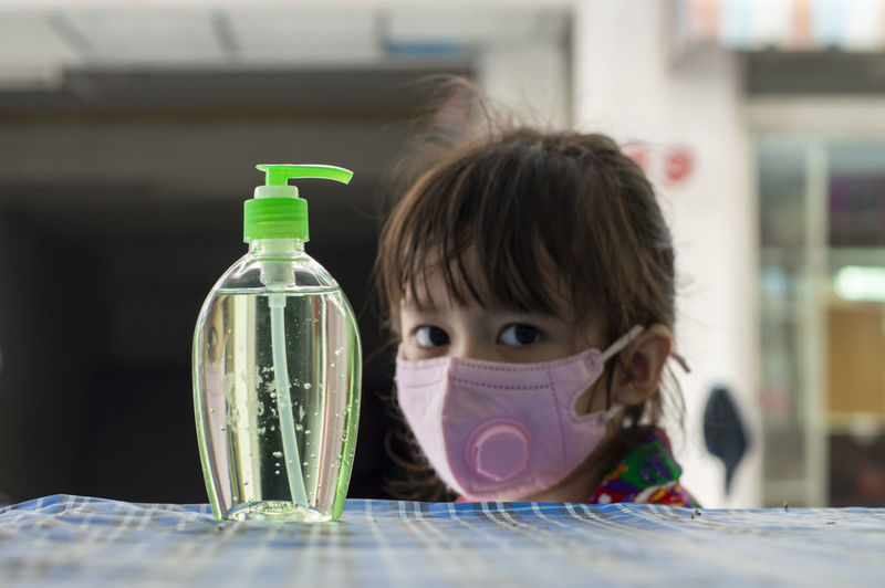 Portrait of cute girl wearing mask by hand sanitizer