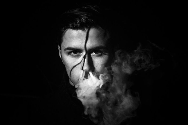 Close-Up Portrait Of Young Man Smoking Against Black Background