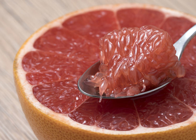 Half of Juicy Ripe Red Grapefruit with slice in a spoon. Citrus; Sweet; Orange; Closeup; Fruit; Red; Food; Ripe; Green; Organic; Tropical; Vegetarian; Fresh; Juicy; Natural; Grapefruit; Vitamin; Lemon; Slice; Background; Diet; Bright; Exotic; Healthy; Ingredient; Cut; Summer; Piece; Health; Raw; Section; Delici Food And Drink Food Close-up Healthy Eating Freshness Indoors  Fruit Citrus Fruit Wellbeing Still Life No People Meat SLICE Grapefruit Red Focus On Foreground Raw Food Cross Section Selective Focus Serving Size