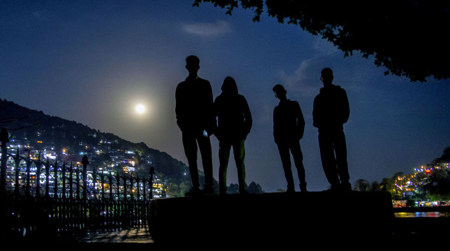 Silhouette people standing by illuminated city against sky at night