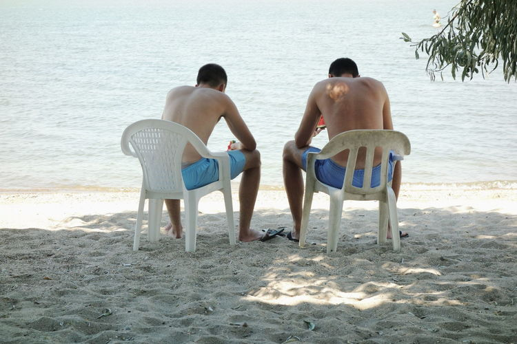 Beach Sand Shirtless Vacations Sea Summer Two People Rear View Togetherness Sitting Men Adult Chair People Leisure Activity Relaxation Full Length Been There. Strand Rest Urlaub The Week On EyeEm