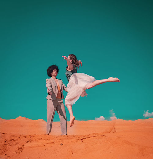 Full length of women jumping on sand in desert against sky