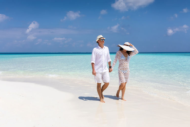 Full length of couple walking at beach against sky