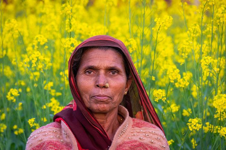 Portrait of woman against yellow flowering plants