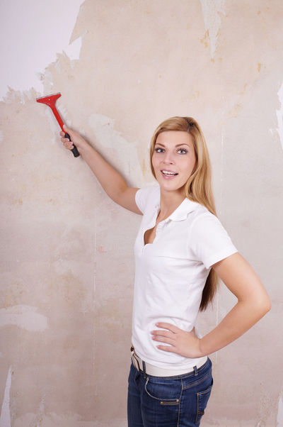 Blonde Casual Clothing DIY Do-it-yourself Female Girl Handywoman Home Home Improvement Lifestyles Real People Redecorating Refurbishment Scraping Wall Wallpaper Woman Young Woman