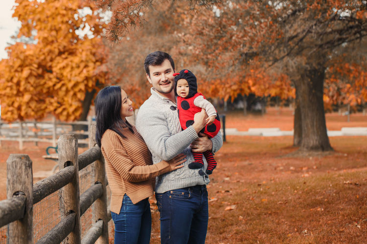 Portrait of father carrying cute daughter while standing with woman in park