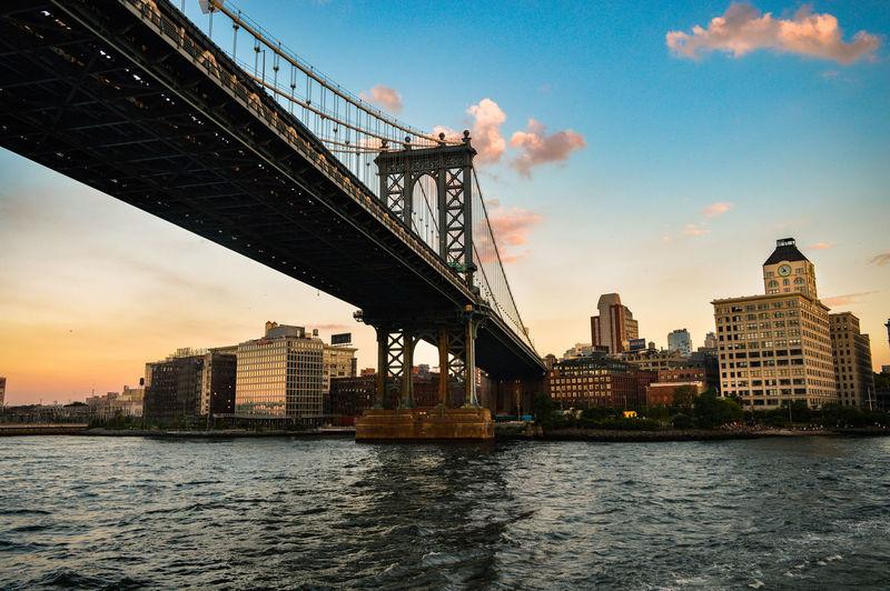 View of suspension bridge in city at sunset