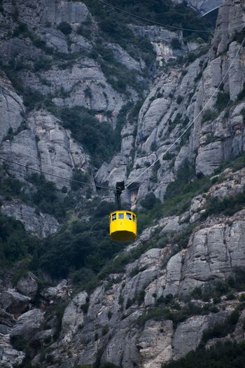 View of overhead cable car against rocky mountain