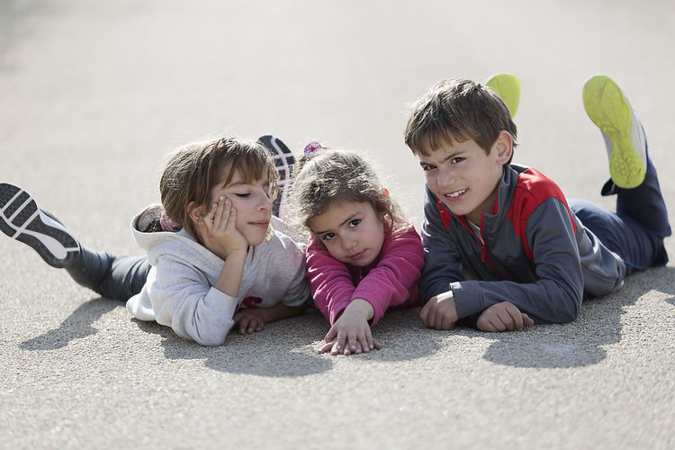 Three children lying on the floor one on top of the other. Horizontal shot with natural light Children Children's Portraits Spanish Tree Children Boys Caucasian Ethnicity Child Childhood Day Innocence Lifestyles Looking At Camera Looking At The Camera Love Outdoors People person Portrait Smiling Togetherness