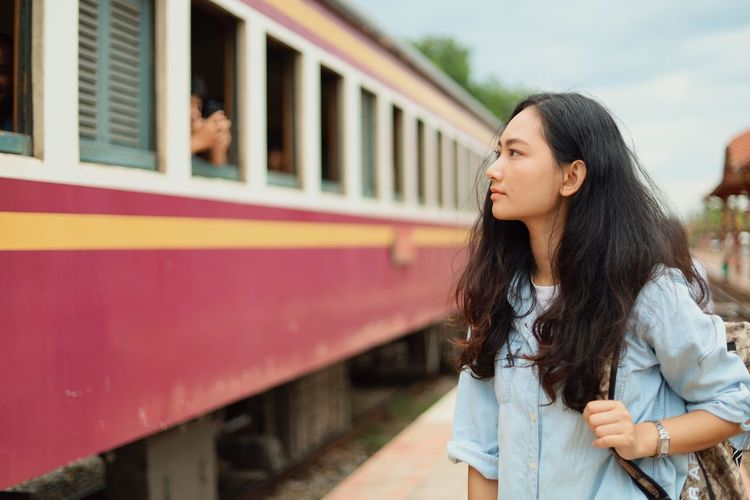 Young Adult Real People Rail Transportation Lifestyles One Person Long Hair Young Women Leisure Activity Train Hair Train - Vehicle Public Transportation Focus On Foreground Standing Hairstyle Casual Clothing Women Waist Up Beauty Beautiful Woman Outdoors Contemplation
