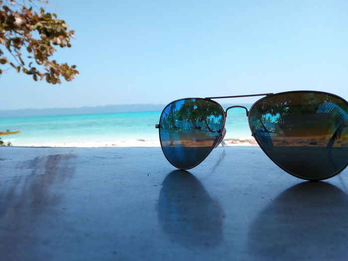 Reflection of sunglasses on beach against sky