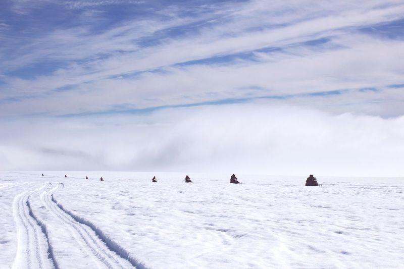 People snowmobiling on snow at vatnajokull against sky