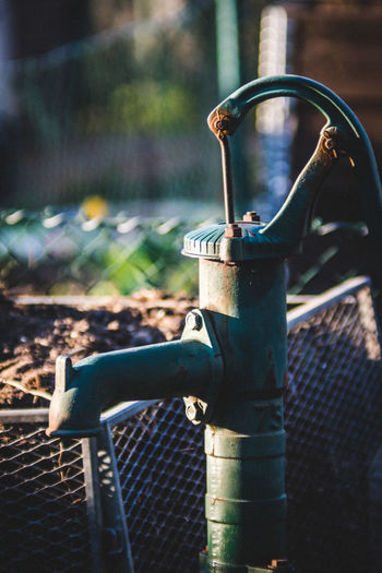 Close-up of faucet on metal fence against blurred background