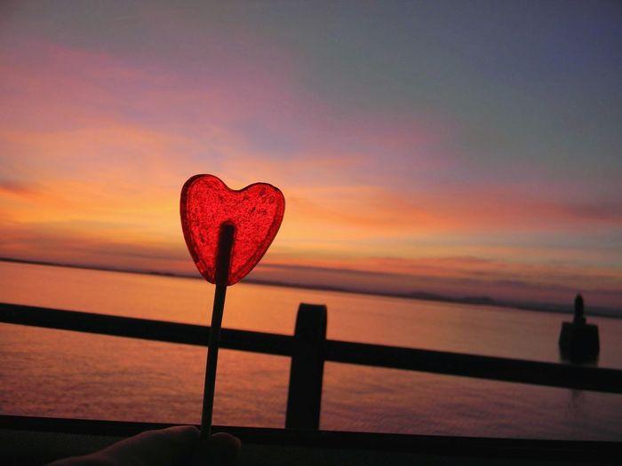 Close-up of heart shape on beach against sunset sky