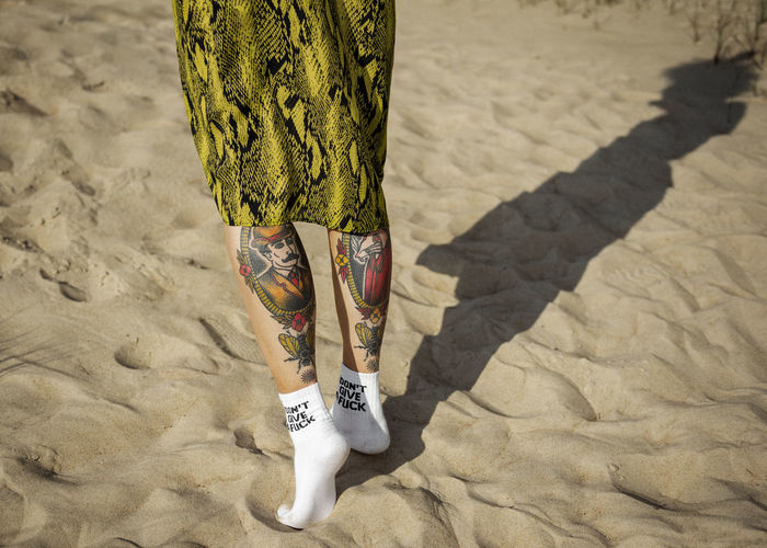 Low section of woman tiptoeing on sand