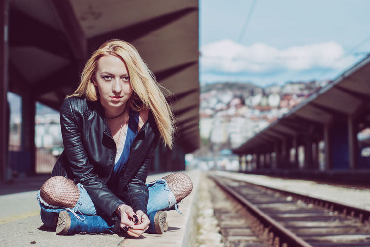 Portrait of young woman sitting at railroad station platform