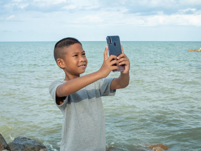 Young man using mobile phone in sea against sky