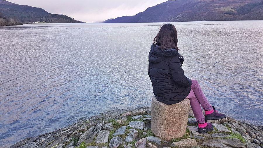 Girl sitting on seat against lake