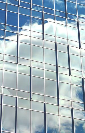Puffy white clouds and blue sky reflected in a modern glass building in Richmond, Virginia Architecture Blue Building City Cloud - Sky Clouds Clouds And Sky Containment EyeEm Geometric Shape Glass - Material Low Angle View Modern Pjpink Reflection Sky Skyporn
