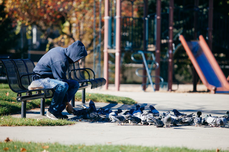 Man sitting on bench at playground