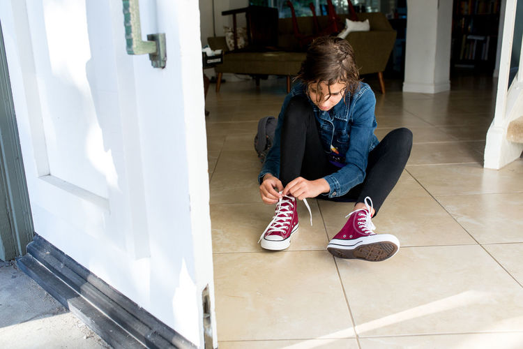 Full length of woman using mobile phone while sitting on tiled floor