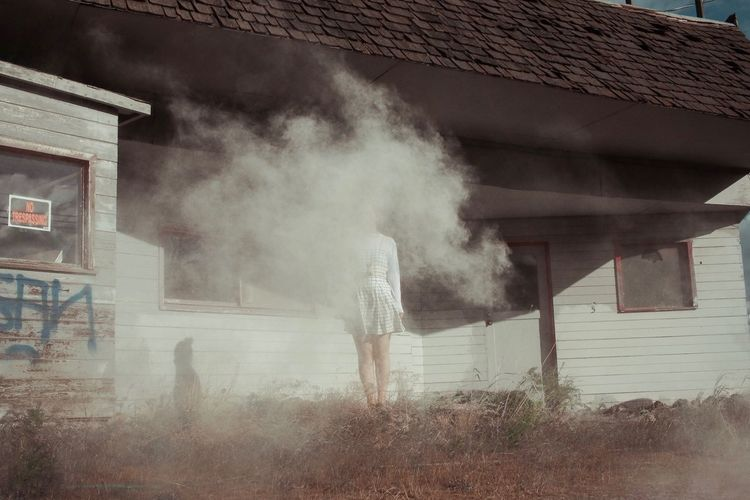Woman standing amidst smoke by house