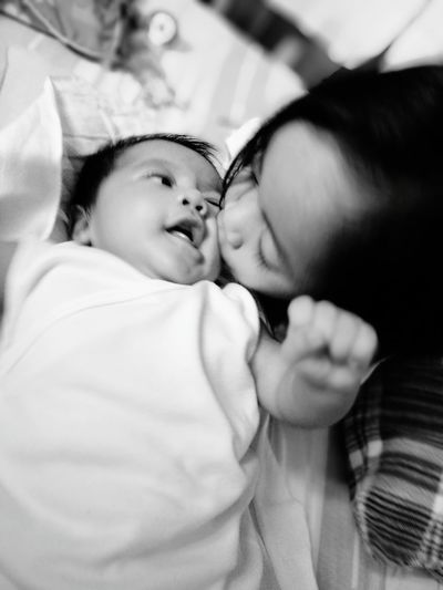 High Angle View Of Girl Kissing Baby Boy Relaxing On Bed At Home