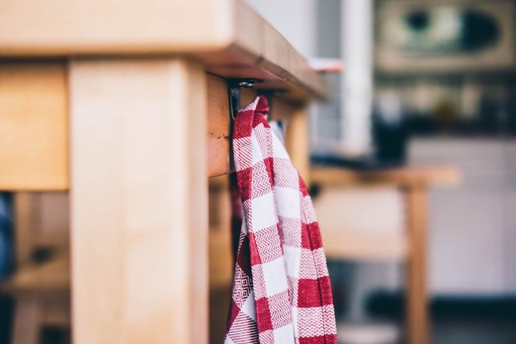Close-up of cloth hanging on wooden table