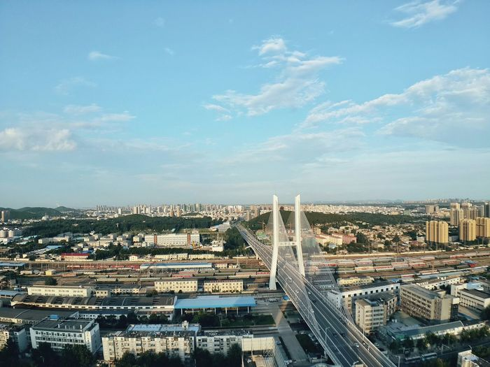High angle view of cable-stayed bridge in city against sky